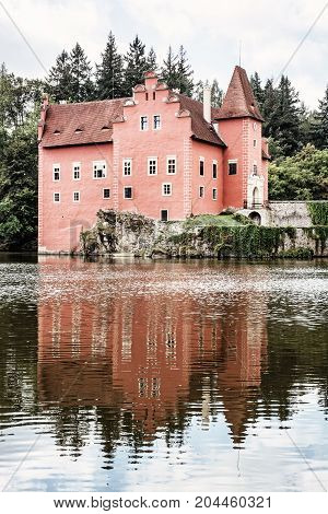 Cervena Lhota is a beautiful chateau in Czech republic. It stands at the middle of a lake on a rocky island. Travel destination. Retro photo filter. Mirrored architecture.