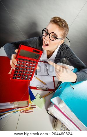 Calculations and results concept. Woman in office calculate company finance. Businesswoman with big red calculator in hand.