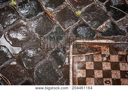 Wet ancient cobblestones on old Rome city road