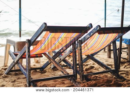 The two rainbow color deck chairs on the beach at Pattaya Thailand.