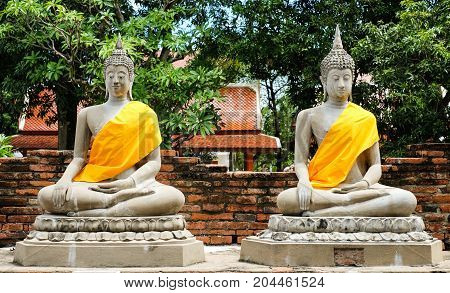 Magical of sandstone buddha (The attitude of meditation) with yellow robe on rectangular platform at
