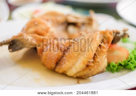 Deep fried snapper topped with sweet fish sauce and vegetable serve on white dish.