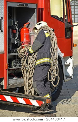 Firefighter at work with a rope next to a vehicle