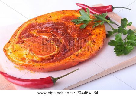Raw Pork ham with spices, parsley leaves and chilli ready for BBQ grilling isolated on white background