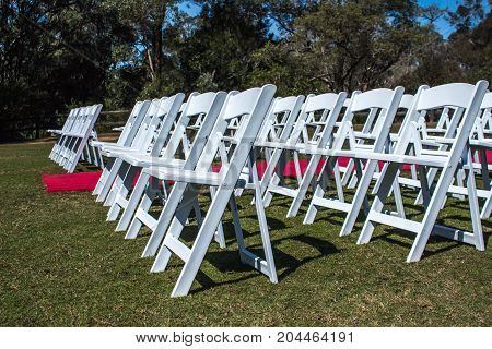 White ceremony chairs set up outdoors with red carpet aisle on green grass with trees in background