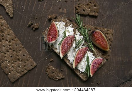 Small loaf of bread with cake cheese, figs and rosemary on the table