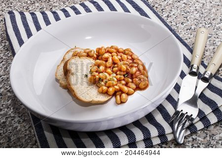 fine dinning with baked beans and slices of bread in a deep plate