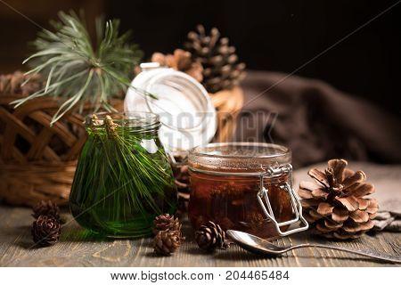 A Jar Of Homemade Jam Made Of Pine Cones And Cedar Honey On A Dark Wooden Background.