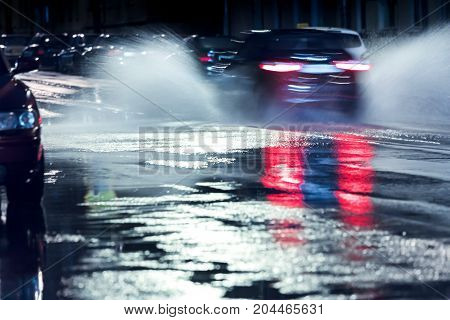 Rainwater Splashing From The Wheels Of Car In Blurred Motion. Rainy Night.