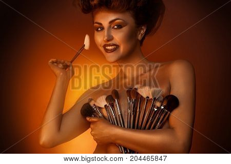 Elegance female smiling at camera with plurality of cosmetic brushes in studio