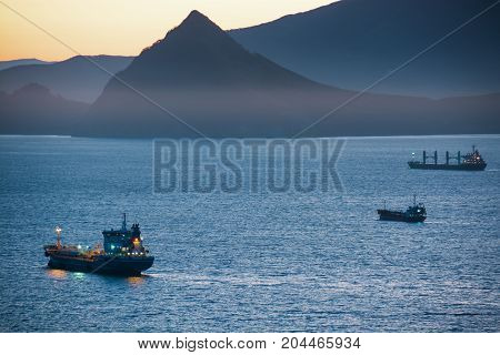 Nautical ships in a harbor at early morning. Tanker ship anchored in the sea bay.