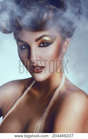 Portrait of nice brunette with make up and smoke background in studio