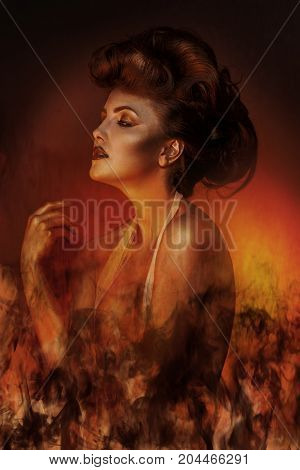 Sexual adult brunette in bandage with fire in studio