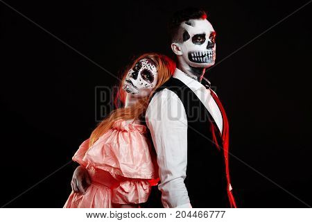 A classy couple, wearing skull make-up for. All souls day. Boy and girl in costumes of skeletons and sugar skull makeup