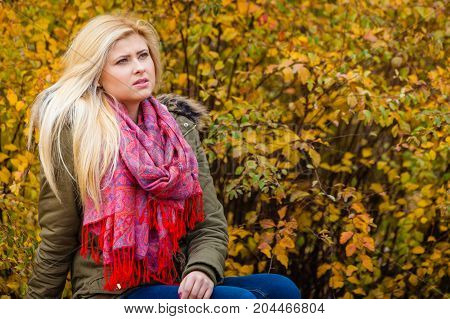Sad looking woman relaxing sitting on bench in park during autumn weather.