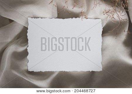 Torn edge paper card on linen cloth with tiny flowers, closup. Wedding stationery mockup. Calligraphy template, invitation.