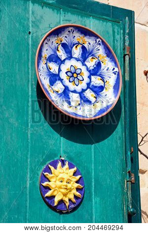 Traditional Maltese plates on a green door in the old town Mdina Malta Europe.