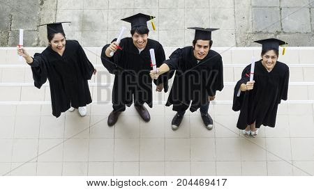 Top view of people students with the Graduation gowns and hat stand and hold diploma in the feeling of happy and graceful.
