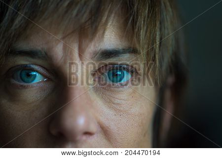 Portrait of mid aged woman with blue eyes close up and selective focus on one eye very shallow depth of field. Dark setting toned image.