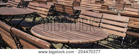 ound empty wooden brown tables with benches on the street