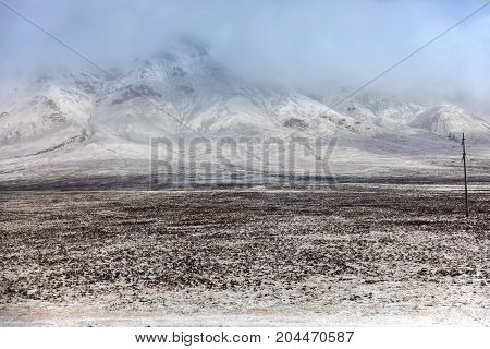 Large mountains covered with snow and fog as background