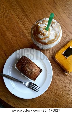 A plastic glass with a cold coffee with a straw in a cafe and a cake on a plate on a wooden table and a yellow wallet.