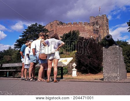 TAMWORTH, UK - AUGUST 9, 1995 - View of the Norman castle with tourists reading an information board in the foreground Tamworth Staffordshire England UK Western Europe, August 9, 1995.