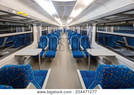 Empty train interior with blue chairs angle shot