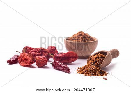 Dry chili peppers and powder on a white background