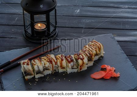 Tasty and delicious traditional japanese sushi roll with seafood and eel fish on black background with candle and shopsticks