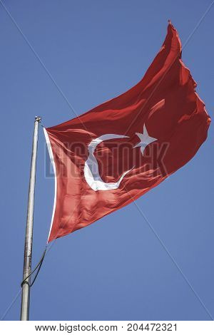 Turkish flag waving against blue sky with copy space