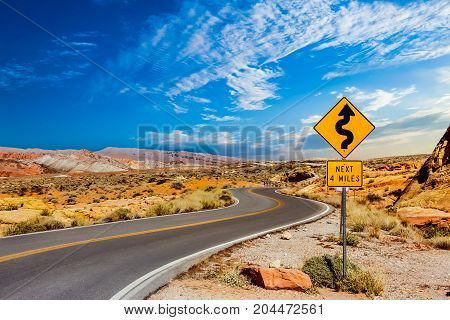 A road sign in the middle of a desert showing curves ahead