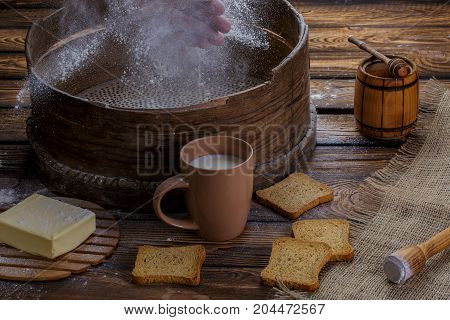 Hands spray the flour over the sieve. around butter crackers a cup of honey milks on a sacking burlap background and a wooden background