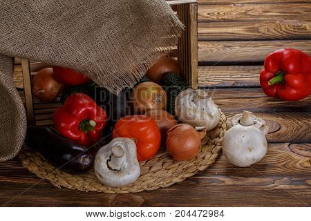 Fresh vegetables in overturned wooden box with burlap over wooden background