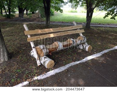 A three-seater bench made by own hands made of logs and boards of a birch
