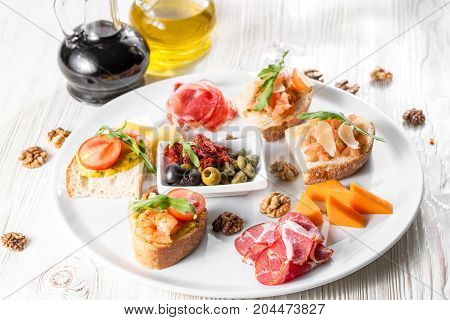 Selection of tasty bruschetta or canapes on taosted baguette and quark cheese topped with smoked salmon, shrimp, prawn, olives, tomato and chorizo sausage