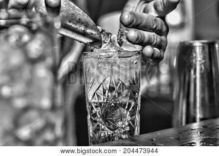 Barman puts ice in a cocktail winter holiday