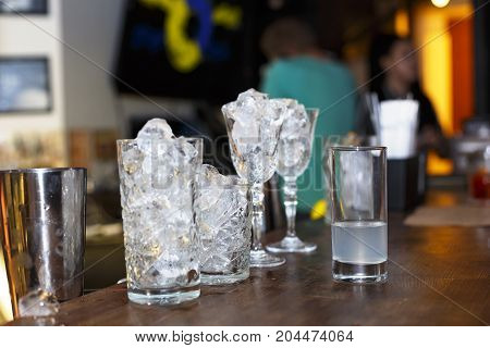 Ice in cocktail glasses on the bar. Preparation of cocktail. winter holiday