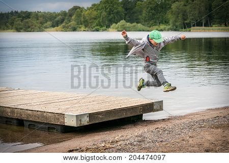 Young playful caucasian boy running in mid-air making a jump from a jetty to the beach.