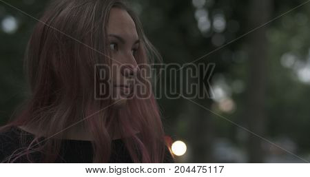 teen girl with purple hair standing in town at night, wide photo