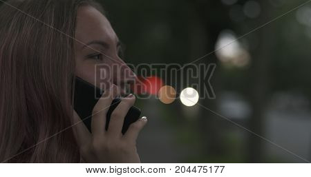female teen talking on the phone on the street at night, wide photo