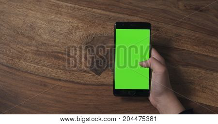 female teen girl holding smartphone with green screen over wood table, wide photo