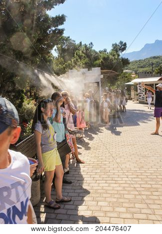 Yalta, Crimea - 11 July, People are cool under the spray, 11 July, 2017. Small Castle Lastochkino Nest and its surroundings.