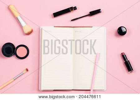 Beauty blogger objects flat lay. Beauty products and stylish female accessories on pastel pink background, top view.