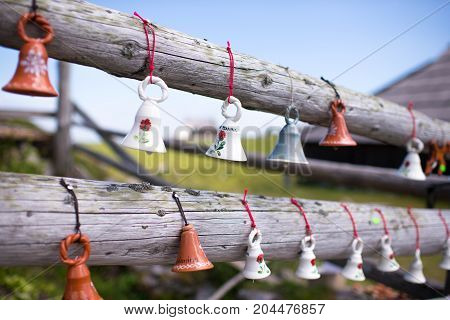 Miniature ceramic cow bells. souvenirs for tourists hanging from wooden fence, typical foe European Alpine Region