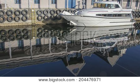 Reflection of the white yacht and berth buildings in the water of the Norwegian fjord
