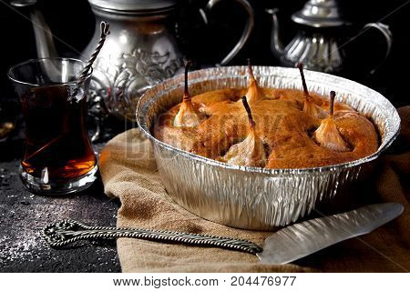 pie with pears in the baking dish with a Cup of tea