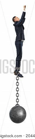 A businessman take a superhero jump in the air with an iron ball still attached to his ankle with a solid chain. Business and hard work. No easy way. Difficult solution.
