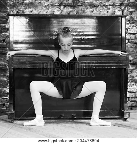 A ballerina and an old piano. Background made of old brick. Music dance education.Black and white photo.