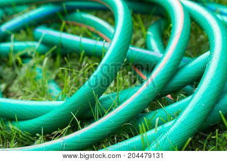 A Green And Orange Hose For Watering The Garden